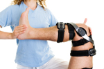 a physical therapist works on an injured knee, in a knee brace
