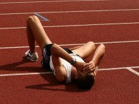 Photo of a runner laying exahusted on a track