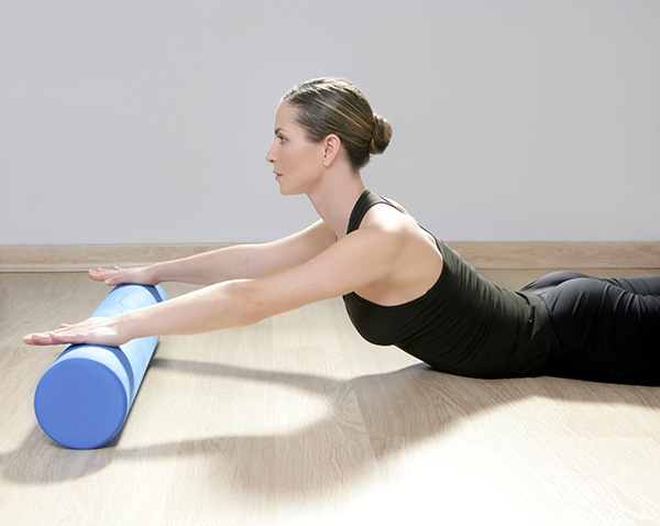 Lady stretching using a foam roller.