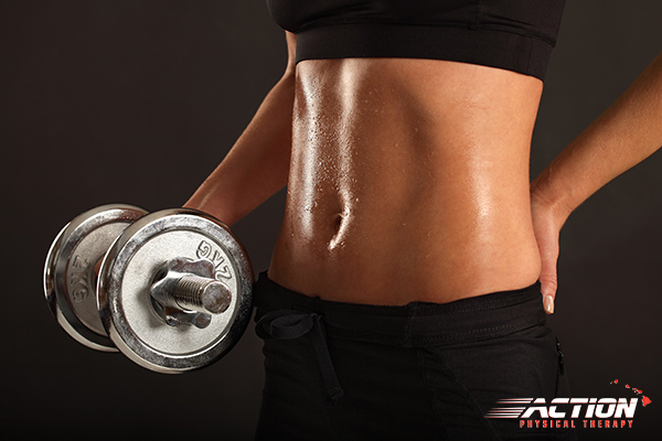 Image of woman's fit stomach as she is lifting weight.