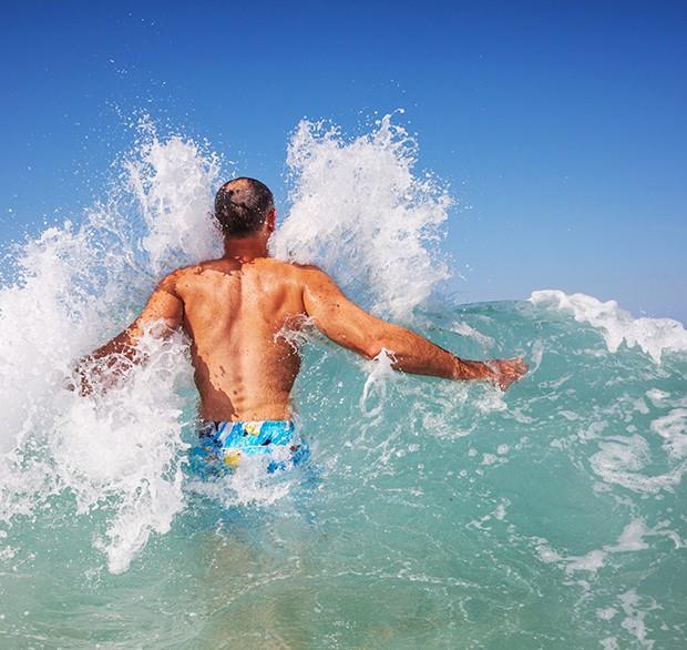 a man jumping through a wave in Hawaii